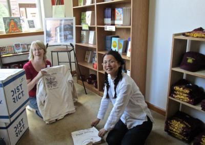 Julia and Rose fold the new T-shirts and re-stock the shelves.