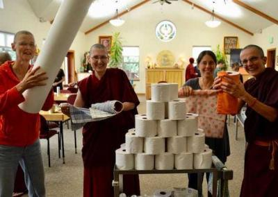 tp rolls stacked by monastic and lay woman