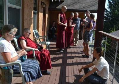 EML-ers, guests, and residents connect on the Chenrezig Hall deck in their break time.