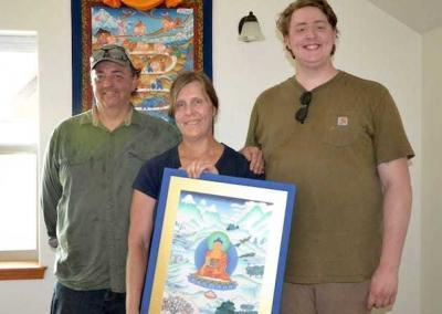 Another family group—Dave, Janet, and Gabe—receive a picture with the Buddha from the Abbey. It's offered in gratitude for their tremendous help in caring for the Abbey and its residents.