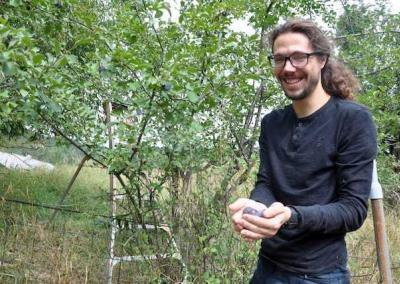 Tristan shows off his harvest of plums from the trees at Tara's Refuge.