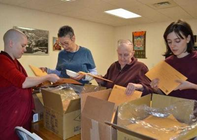 After hours of packing and labeling about 500 copies of Unlocking Your Potential for inmates in the US, Ven. Lamsel, Claudia, Ven. Jigme, and Sydney sort the books for the post office.
