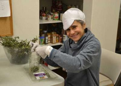 Maria prepares our garden herbs, like marjoram, for use in the kitchen.