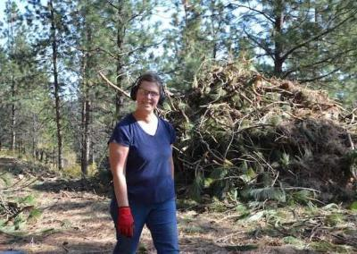Janet organizes piles of branches for the chipping team.