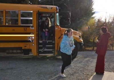 The bus arrives! Ven. Damcho, with her great teacher's enthusiasm, welcomes the first students.