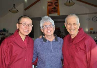 Georgette generously offers maroon jackets for all 16 monastics! Vens. Damcho and Chodron receive their jackets right before their departure for Asia.