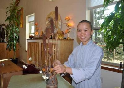 Ven. Thuc offers a lovely flower arrangement to the Buddha.
