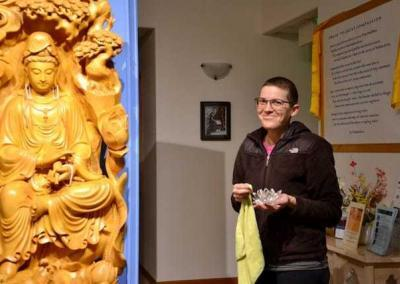 Stacy offers water bowls every day to Kuan Yin in Chenrezig Hall.