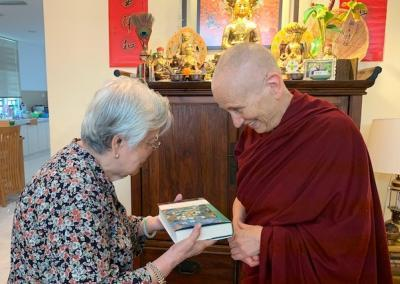 Ven. Chodron delights in presenting a signed copy of Following in the Buddha's Footsteps from Kenryuu to his elementary school teacher Ms. Chew.