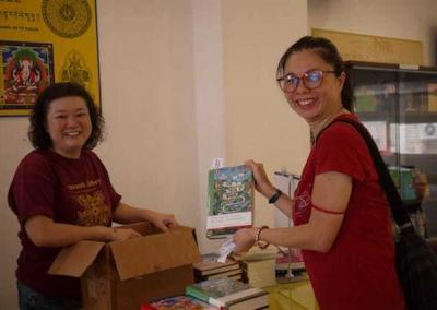 FOSA-S volunteers Jessie and Cheng Cheng show off Volume 4 in the Library of Wisdom and Compassion.