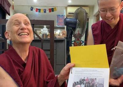 Ven. Chodron delights in a card presented by the lamrim class.