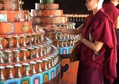 Ven. Jampa makes butter lamp offerings for the welfare of all sentient beings.