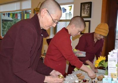 "Vens. Tsepal, Lamsel, and Nyima prepare the altar for the Guru Puja: ""May all beings attain the seven jewels of an exalted being."""