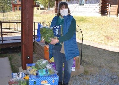 Woman with mask delivers food to monastery.