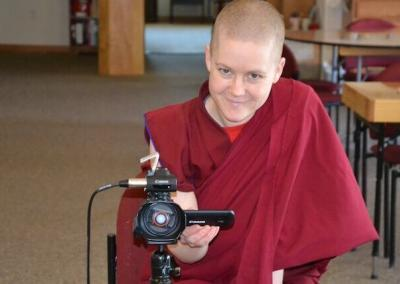 Nun operates video camera.