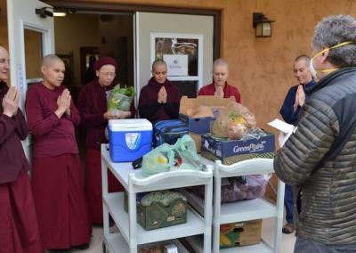 Person donates food to monastics.