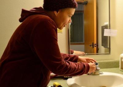 Nun repairs faucet.