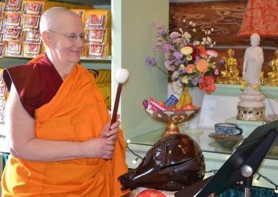 Nun plays ritual instrument.