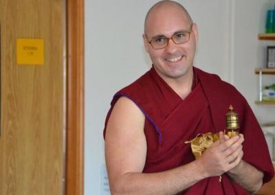 Monk holds prayer wheel.