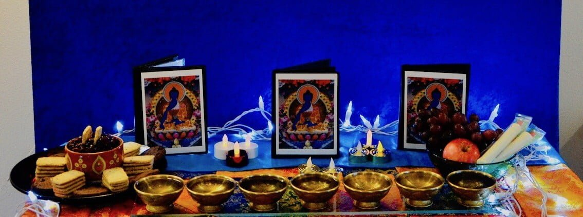 Medicine Buddha cards and offerings on altar