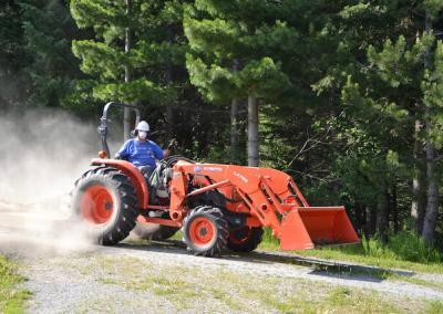 Man on tractor mows grass on forest trails.