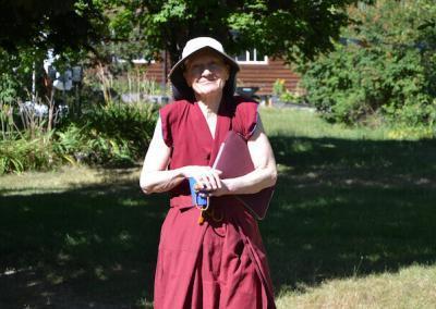 Nun walks in garden.