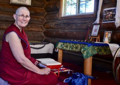 Nun meditates in log cabin.
