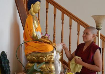 Nun dusts Buddha statue.