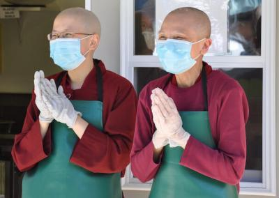 Nuns accept food offering wearing masks.