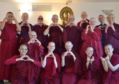 Nuns make heart signs.
