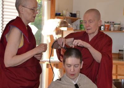 Nuns shave monastic trainee's head.