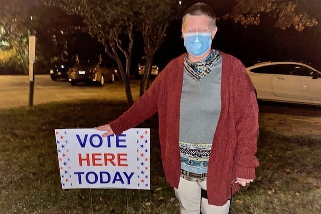 """Masked woman standing with a sign, """"Vote here today."""""""