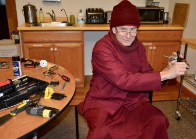 Monk fixes door handle.