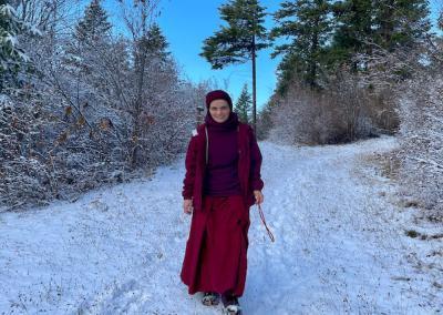 Nun walks in forest.