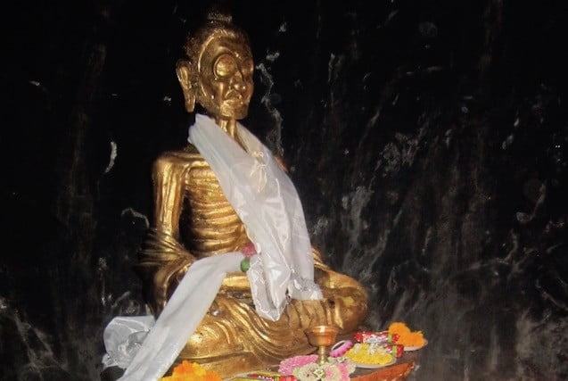 Gold statue of emaciated Siddhartha in a dark cave.
