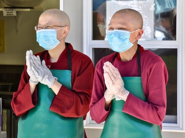 Two nuns in masks with prayerful hands.