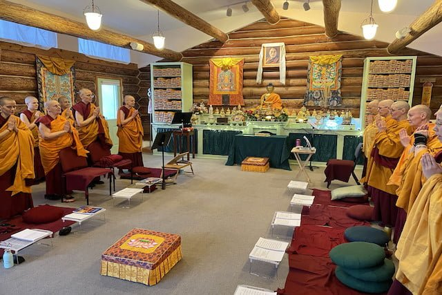 Monastics stand in Meditation Hall.