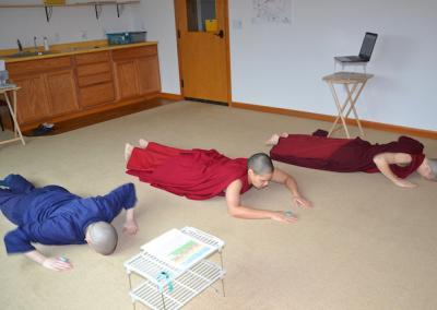 Nuns and trainee prostrate to buddhas.
