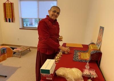 Nun prepares Buddha altar.