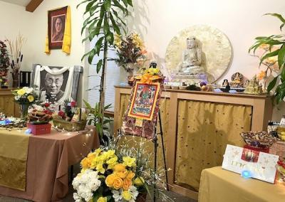 Two tables of flowers and food in front of an image of Tara