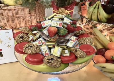 A dish of fruit and sweets surrounded by other food offerings