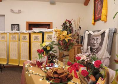 A table of offerings with pictures of His Holiness the Dalai Lama in the background