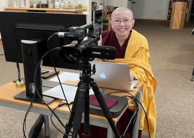 Nun smiles behind videocamera