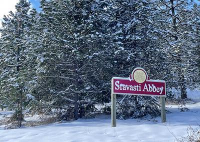 Sign in front of snow-covered pine trees