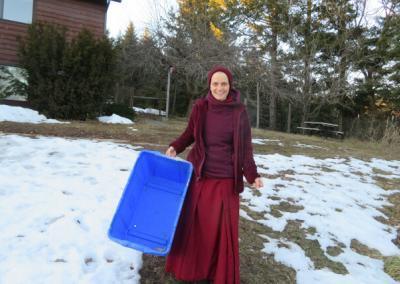 Nun holds empty blue recycling bin