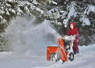 Smiling nun uses snowblower