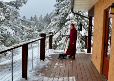 Monk shovels snow on deck