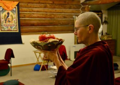 Nuns holds up food offering bowl in meditation hall