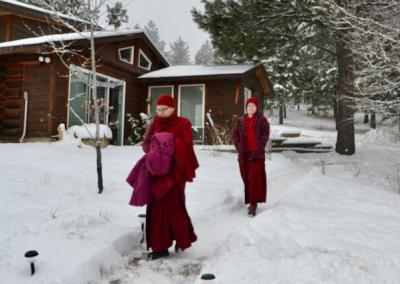 Two nuns walk down snowy path from meditation hall