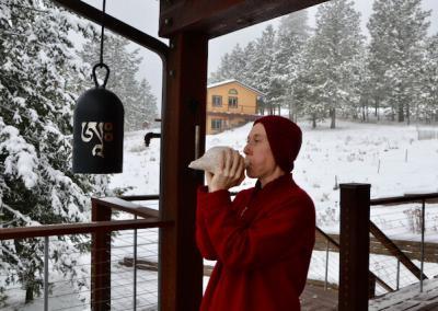 Nun blows white conch shell outside